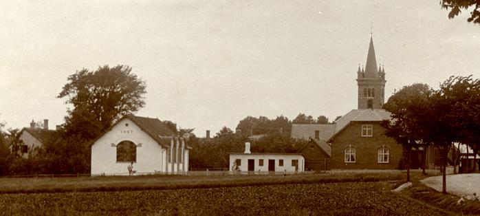 Ugerløse skole set fra Hovedgaden med den nye gymnastiksal fra 1907 og den røde forskole nærmest Hovedgaden. De små hvide udhuse er lærernes vaskehuse – et til hver lærer.