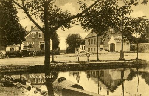 Byens Gadekær ca. 1915 - Billede 53 I det lille hvide hus th. holdt sognets brandsprøjte parkeret. Det røde hus er i dag nedrevet - her ligger i dag urnekirkegården. Tv. er det Østrupvej 122 som dengang var byens sæbehus, senere forretningen Tatol, og senere endnu en bank.