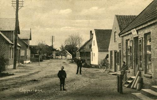 Hovedgaden ca. 1905 - Billede 23 Th. er det Chr. Olsens Købmandshandel, Hovedgaden 29. Den hvide gavl er smedjens (bemærk hesten), og huset efter er bagerens hus i nr. 21 - man kan ane udhængsskiltet med kringlen.