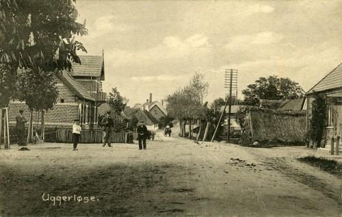Hovedgaden ca. 1905 - Billede 29 Tv. er det Hovedgaden 7. Bemærk det lave stråtag på modsatte side af vejen. Det lille hus er for længst revet ned. Se også det lille hvide hus med stråtag længere nede af Hovedgaden på venstre side - det er også revet ned.