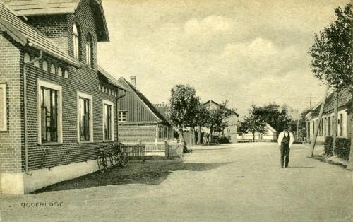 Hovedgaden ca. 1905 - Billede 30 Tv. er det nr. 28. Det næste hus med strå på gavlen er revet ned. Her ligger nr. 26 nu. Gården længere fremme på venstre side er Toftegården. Th. er det bagerens hus nr. 21 - bemærk udhængsskiltet med kringlen.