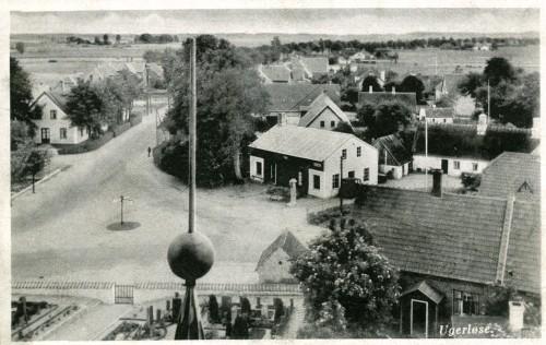 Hovedgaden mod syd ca. 1935 - Billede 36 Hovedgaden set fra kirketårnet. Dem store bygning nederst th. i billedet lå i kirkegårdsmuren - men er nu nedrevet for at gøre plads til urnekirkegården. Bemærk også Smedegårdens bolig med stråtag.