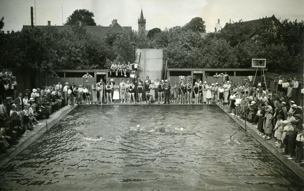Ugerløse Friluftsbad ved indvielsen den 20. august 1933 Flere end 2.500 mennesker var mødt op til indvielsen, så svømmeopvisningen måtte vises over flere omgange, da der ikke var plads til alle omkring bassinnet.